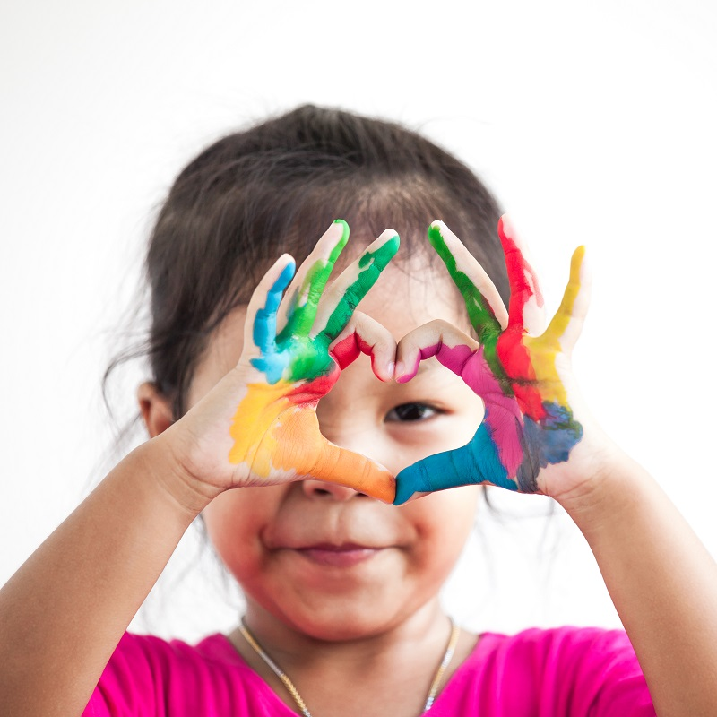 Cute asian child girl with hands painted make heart shape on white background